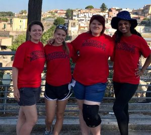 Professor and three students in University of Mississippi t-shirts pose in front of ancient Herculaneum.