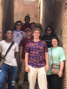 Eight classics students pose in a stairwell in Roman Ostia